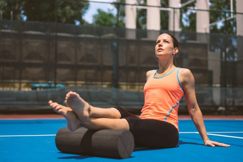 Dr. Magdalena Schauenberg sitting on the ground, using a foam roll underneath her legs. Adidas; GamePlan A; Mindset; Habits; Workout; Relaxation; Foam roll; Training; Performance