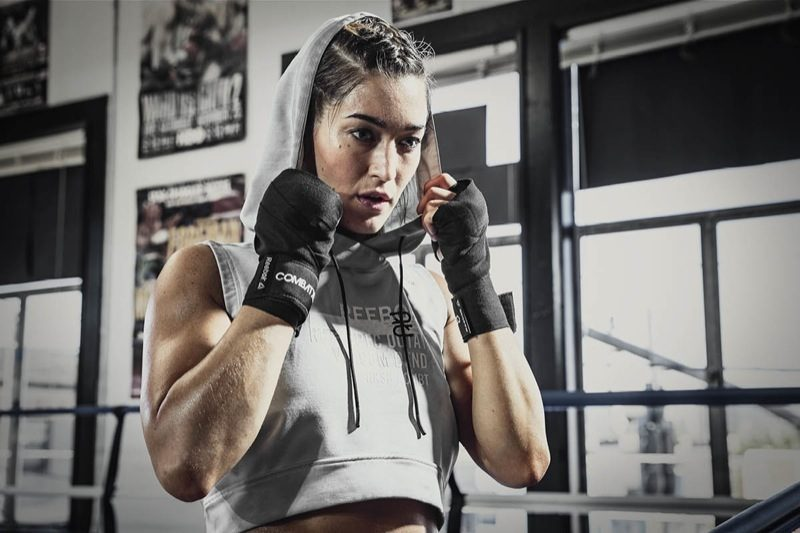 A female athlete wearing boxing bandages is arranging her hood while breathing deeply. Combat; adidas; Reebok; GamePlan A; Preparation; Success; Mindset; Energy; Workout