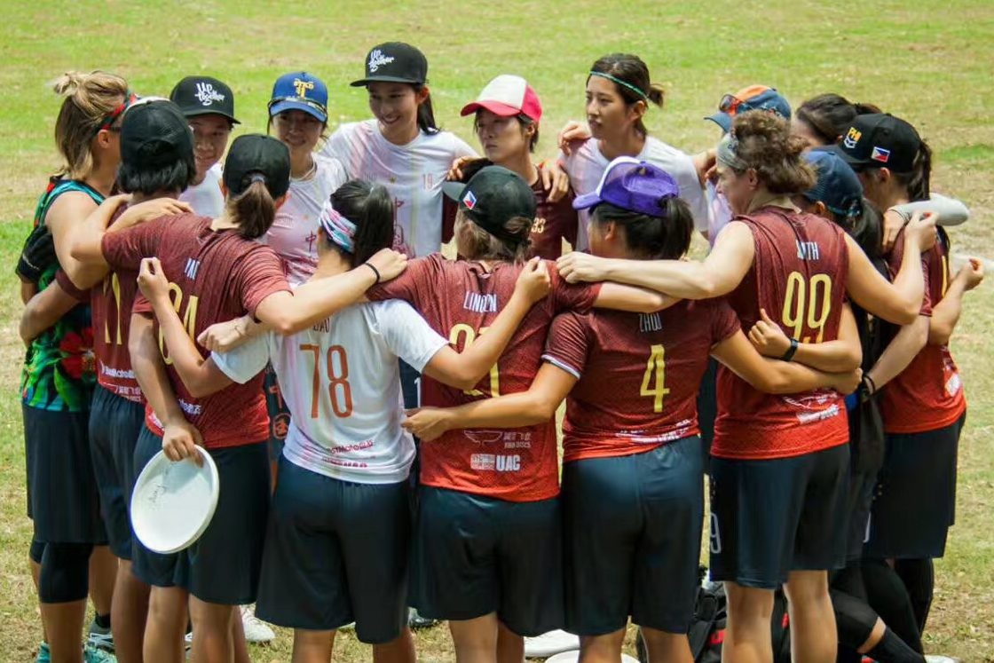Woman's frisbee team circles up in a huddle on the field.