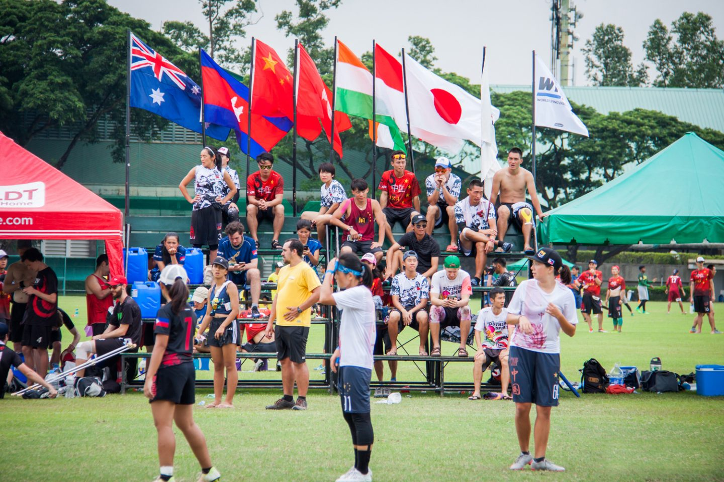 Chinese female ultimate frisbee athletes compete in a tournament with international flags flying in the background of the bleacher seating.