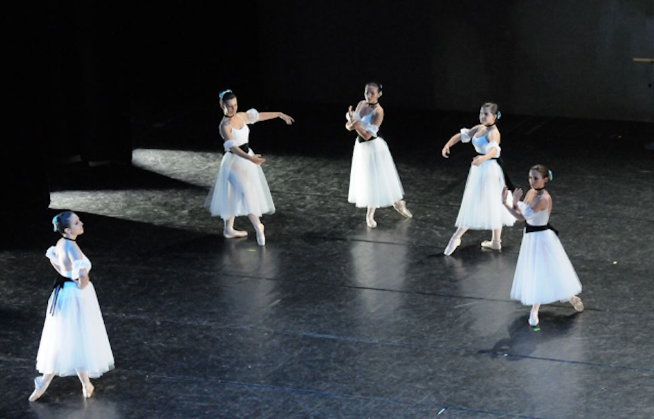 Five girls are dancing ballet on a black stage dressed in white, ballet show, ensemble