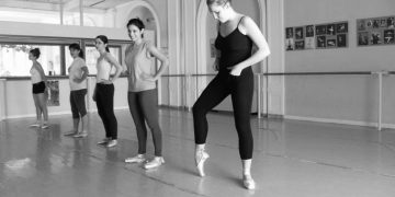 A female ballet ensemble is practicing in a black and white setting, ballet_practice_improvement_patience