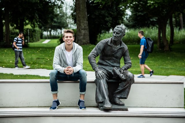 An intern sits next to a statue of Adi Dassler on the adidas headquarter campus.