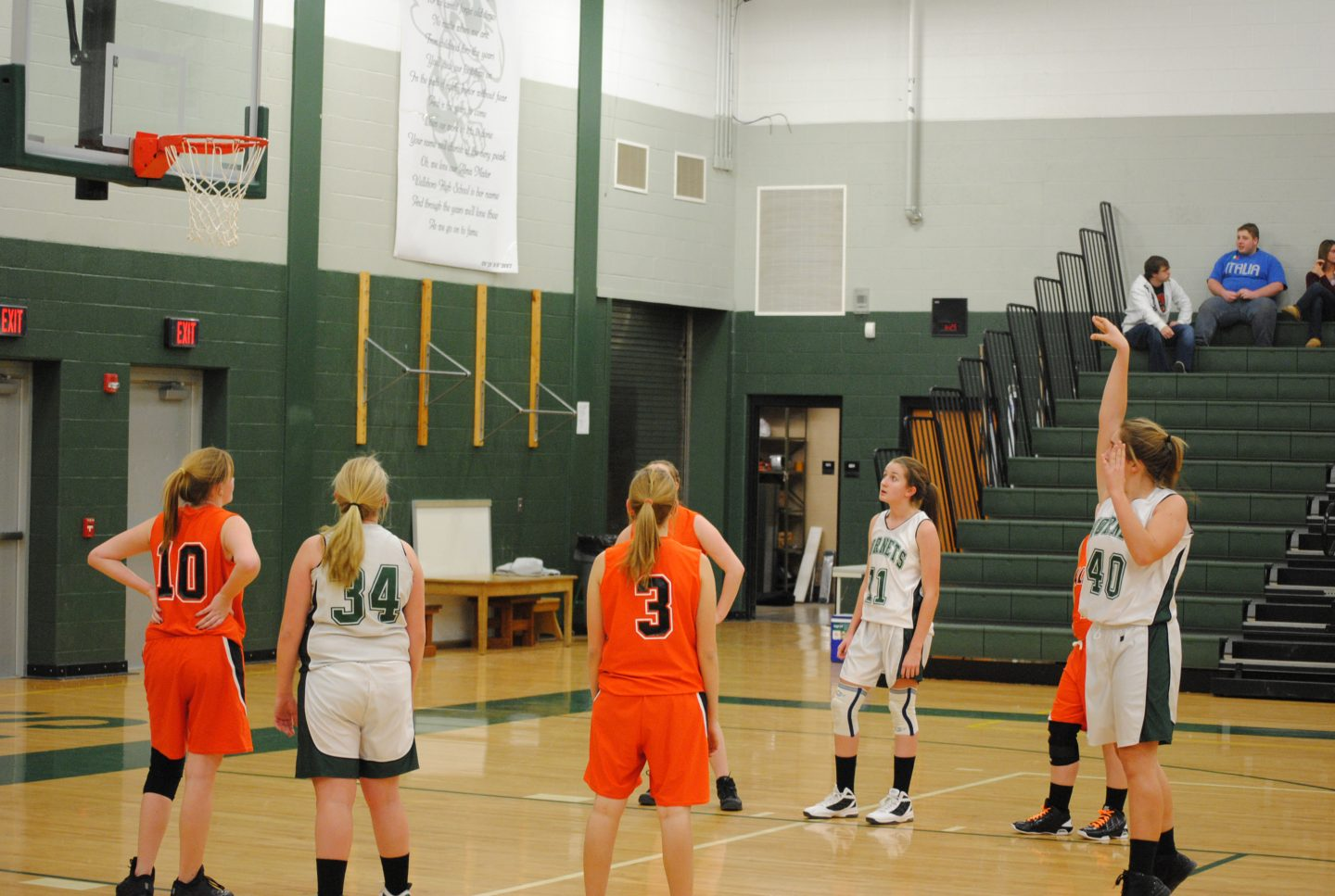 A female basketball team is playing and one girl is at the free throw line throwing the ball to the basket, team sport, winning, motivation