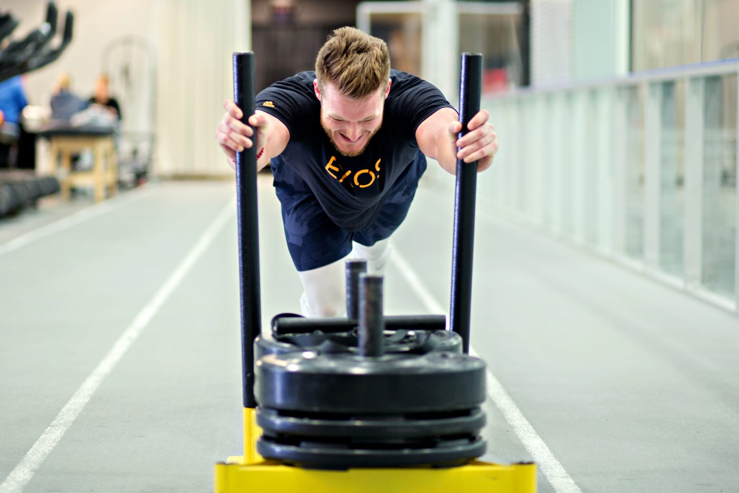 An EXOS trainer is working out to reach his goals and new year resolutions in a gym_reaching goals