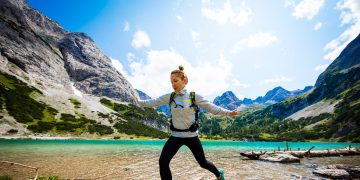 A sporty woman hiking in the mountains with a lake in the background. Outdoor-Hiking-Comfort Zone-GamePlan A-adidas, self-improvement, Terrex, Austria, Alps