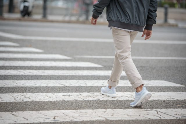 Man from behind crossing a street wearing white sneakers. Runtastic-Steps-Health-adidas-GamePlan A, steps, fitness
