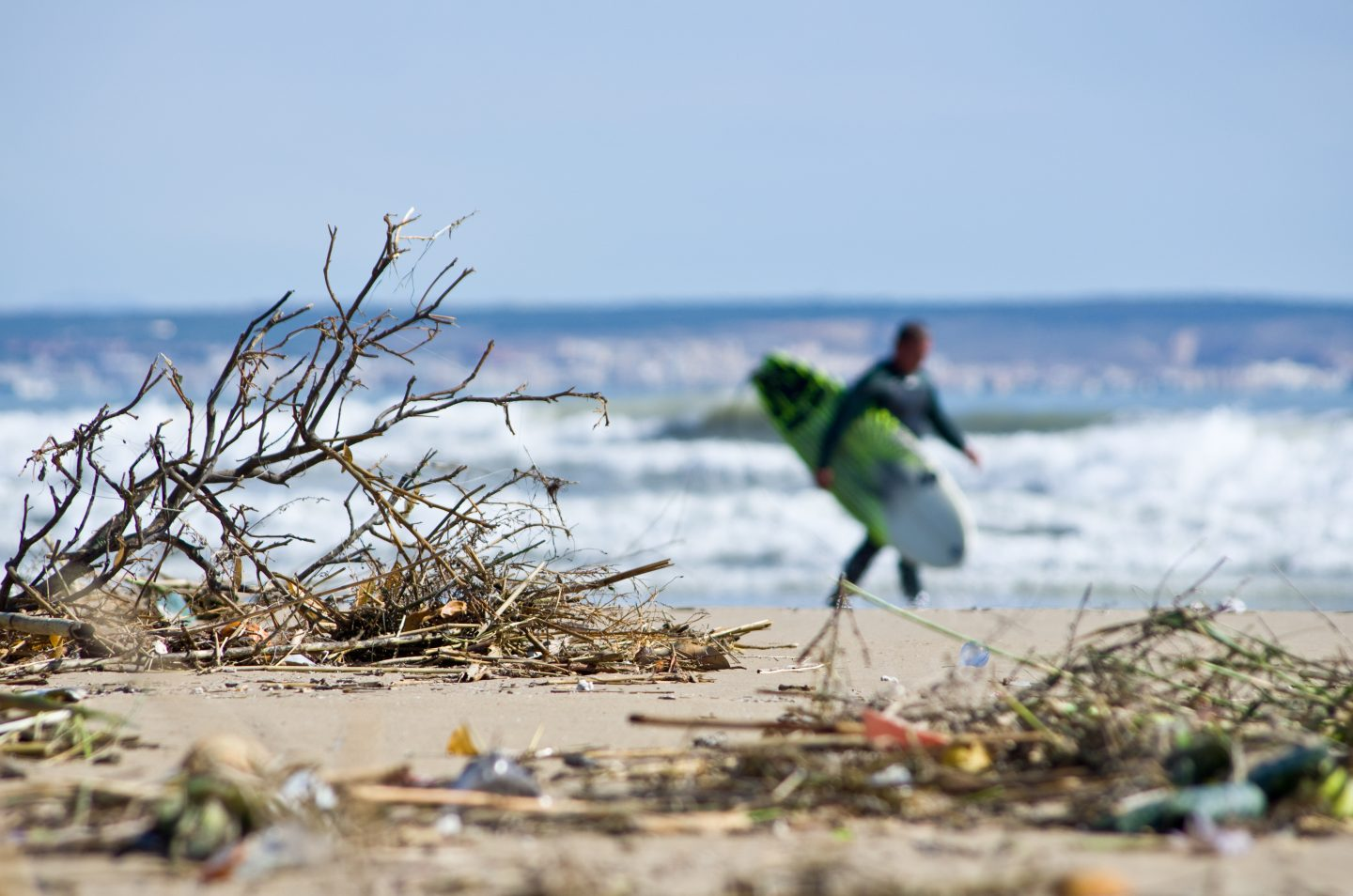 Looking at a beach with a surfer running in the background_ Photo of blurred beach_ trash_pollution_activist