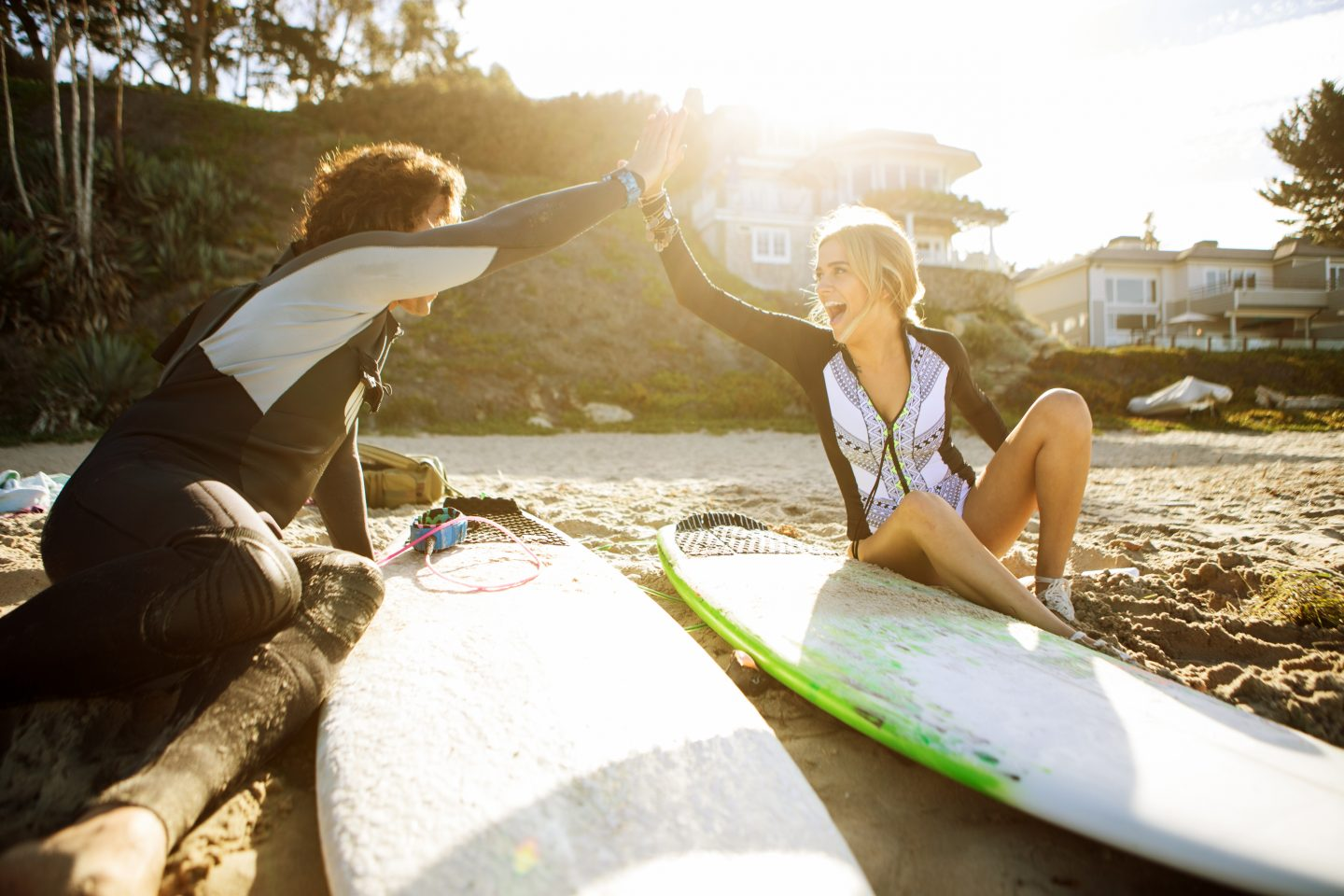 Friends cheering each other at the beach sitting beside their surf boards_ Surfing_Friends_Sunset