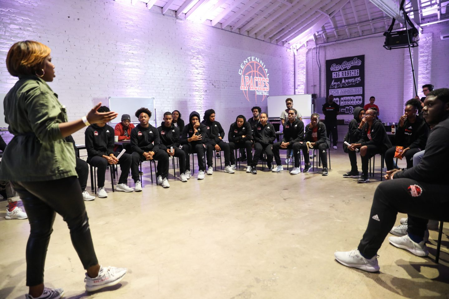 A woman talking in front of high school pupils. adidas, GamePlan A, communities, support, athletes, corporate social responsibility
