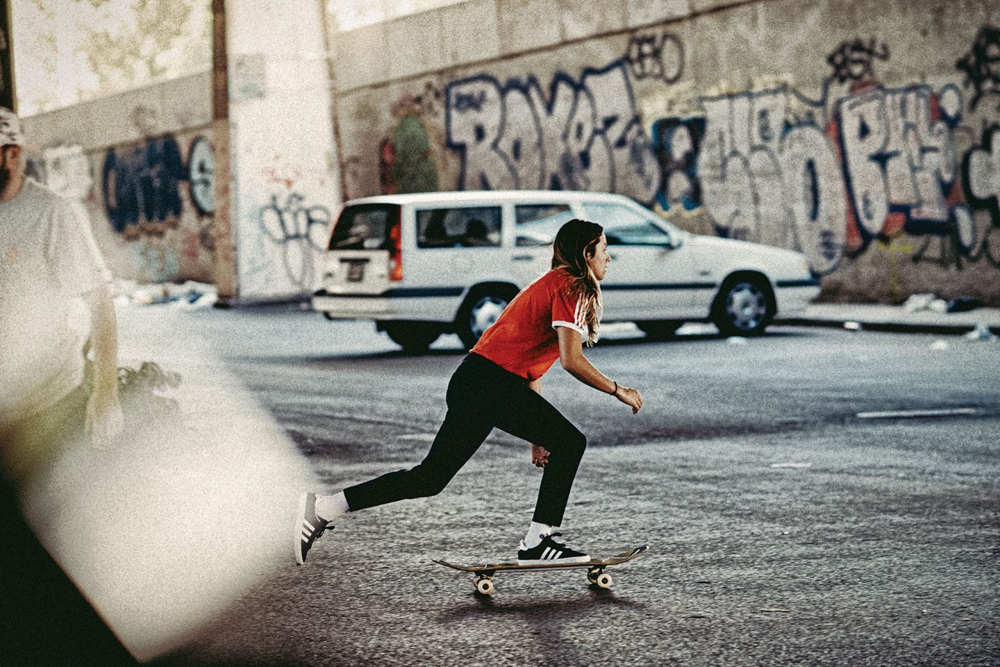 Girl skateboarding through the street. Skate board. Skater. GamePlan A.