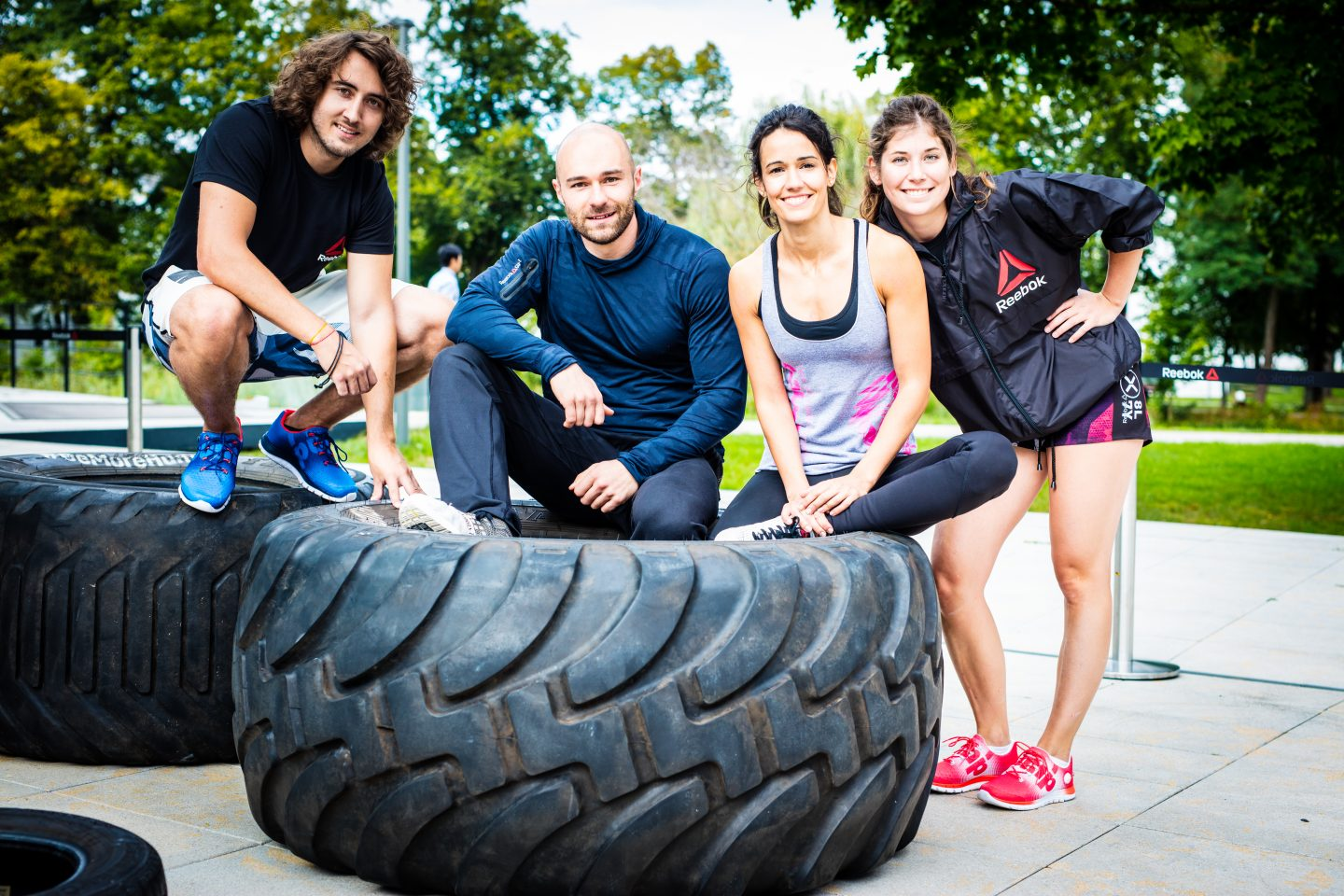 A group of friends resting on two large tires after a great workout. Reebok, fitness, workout, team, friends, accomplishment.
