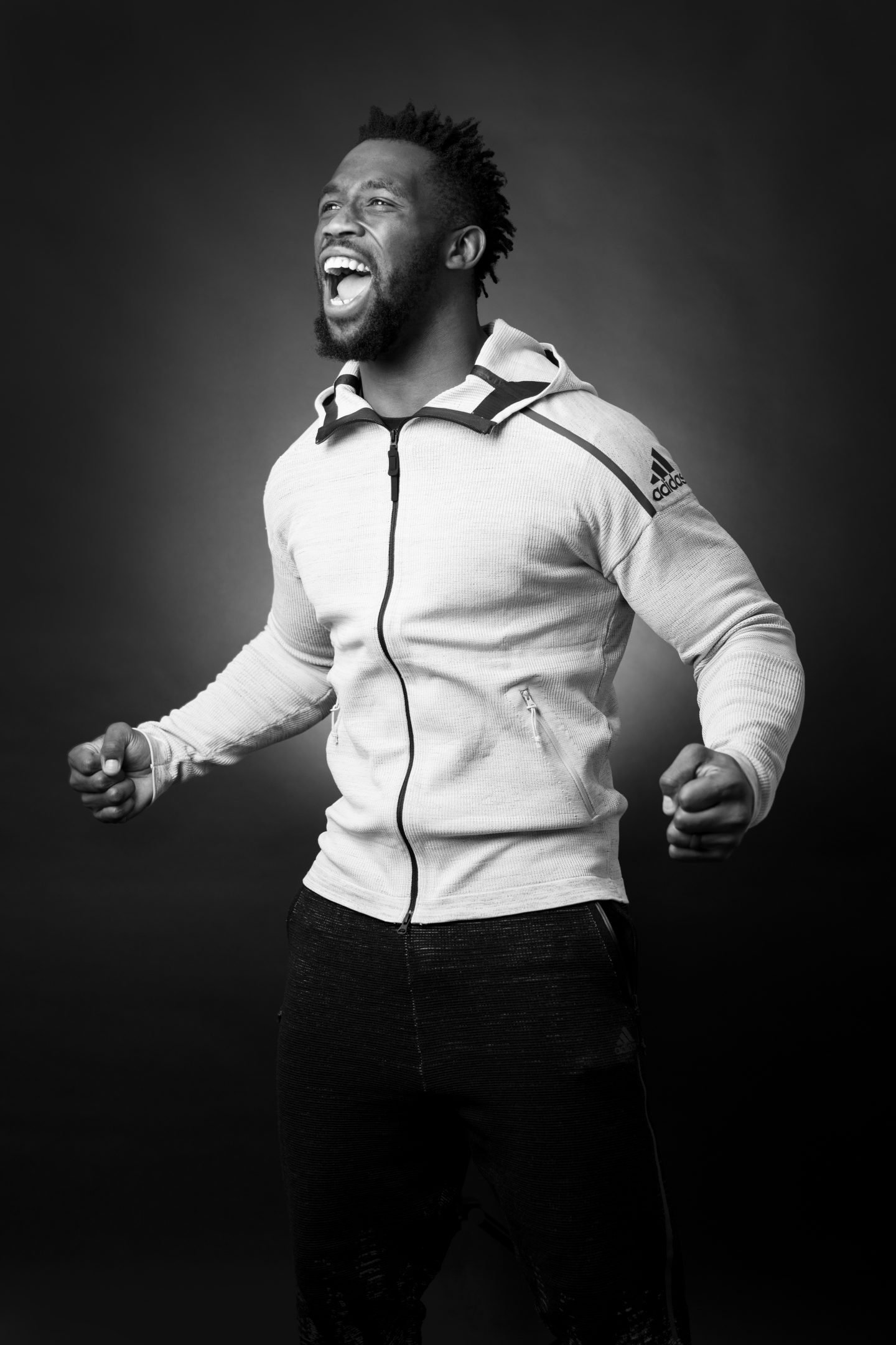 Siya Kolisi stands tall roaring in happiness clenching his fists. Athlete, leadership, success, rugby.