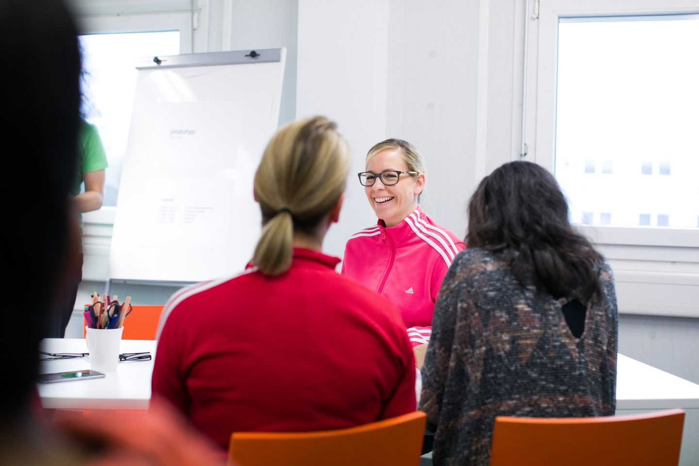 Female adidas employees sit together deep in discussion in a meeting. Meeting, Workplace, Colleagues, Motivation.