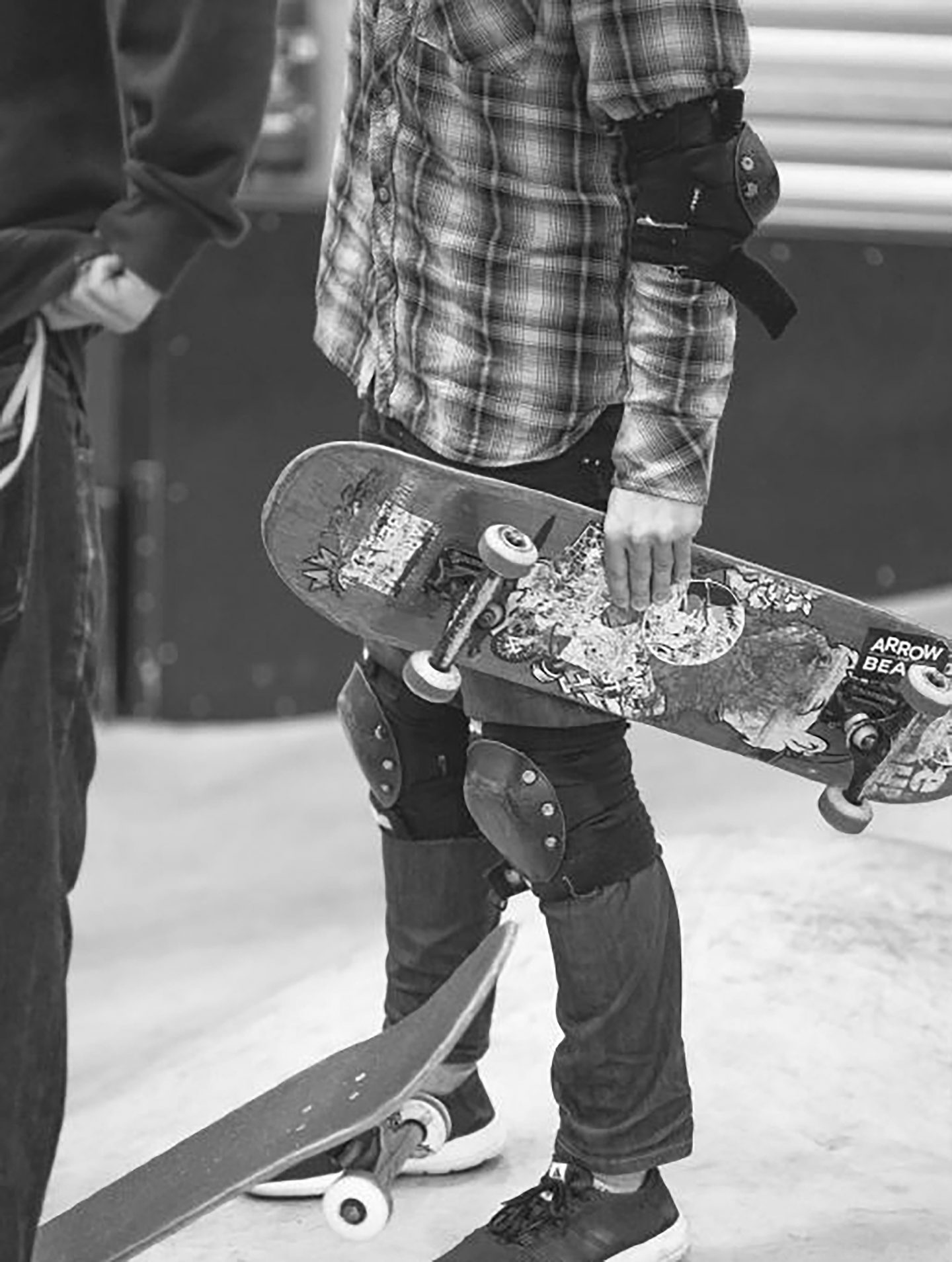 Black and white photo of a skater boy wearing protective knee and elbow pads getting ready to skate. skater, determination, skateboard, hobbies.,