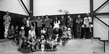 All the budding skateboarders stand and sit around indoors smiling and holding their skateboards. skateboarding, community, career, skater.