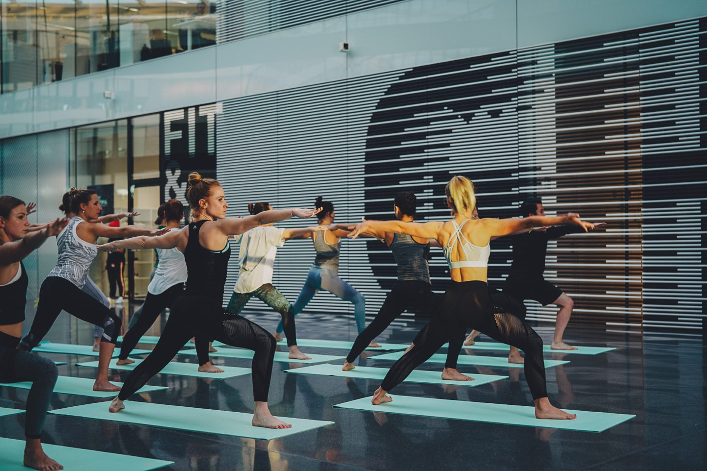 A group of yogis practicing yoga in an office building at adidas. employees, creativity, flow, yogi, leadership, GamePlan A, adidas HQ, Laces, warrior pose