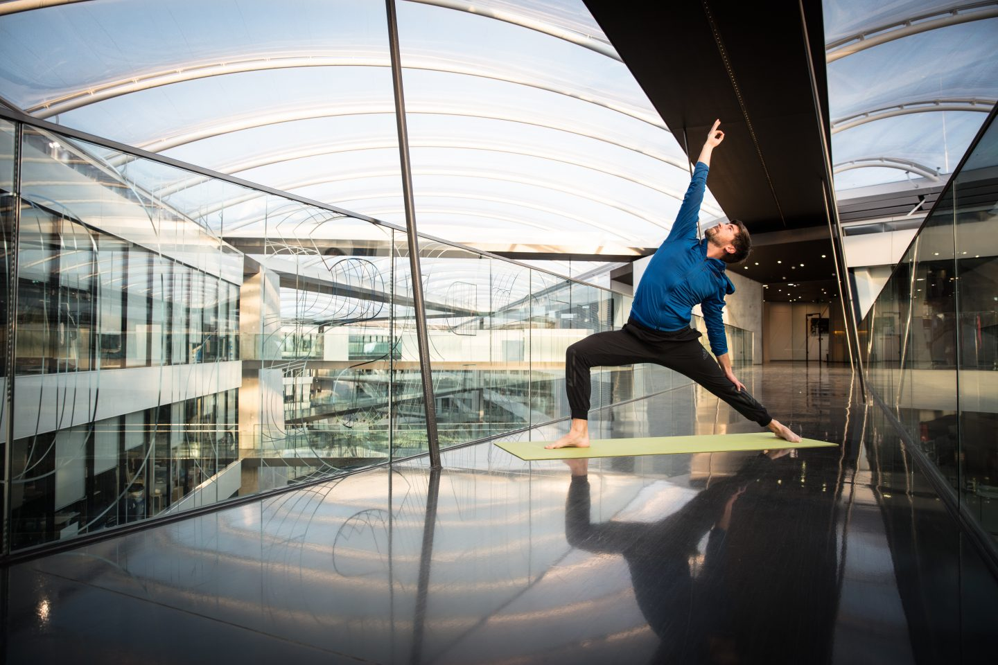 Man doing yoga in the center of his workplace. yoga, well being, sport, passion.