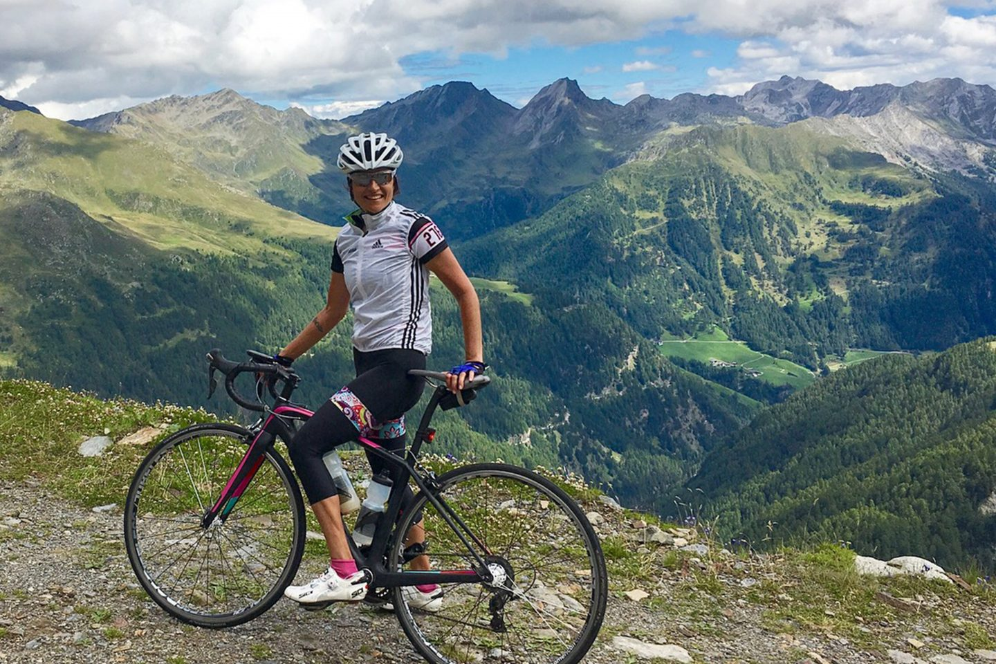 A female cyclist takes a rest on her bike on top of a mountain range on a sunny day. cycling, biker, biking, passion, sport, hobby, fitness, motivation.