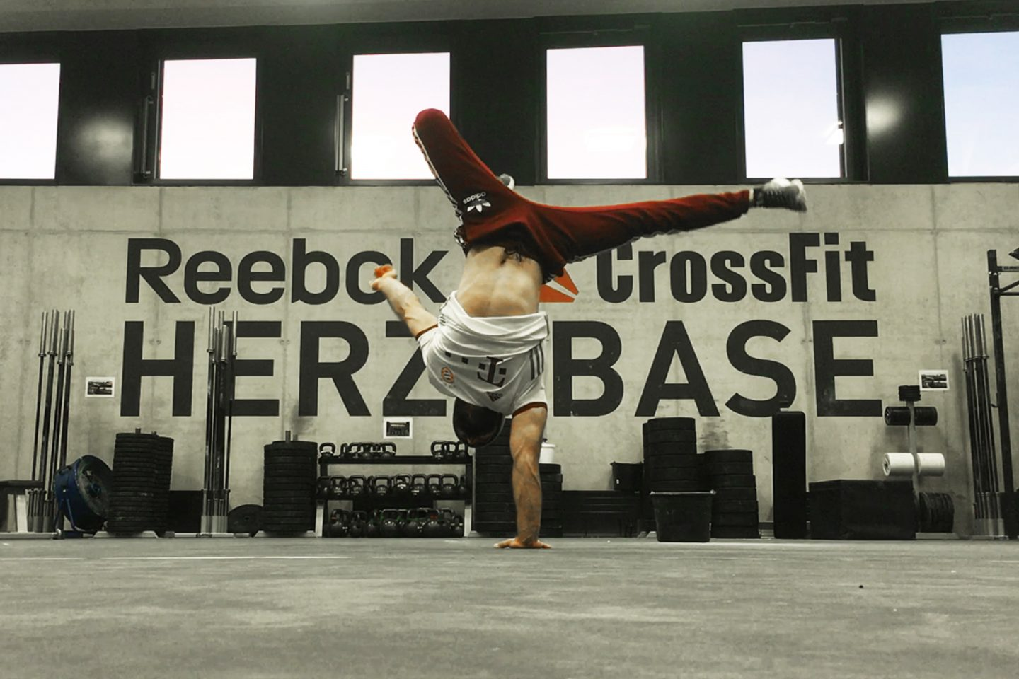 Breakdancer does a handstand side kick in Reebok Crossfit Herzo Base gritty gym as part of his passion for dancing. dancing, passion, dancer, hobby.