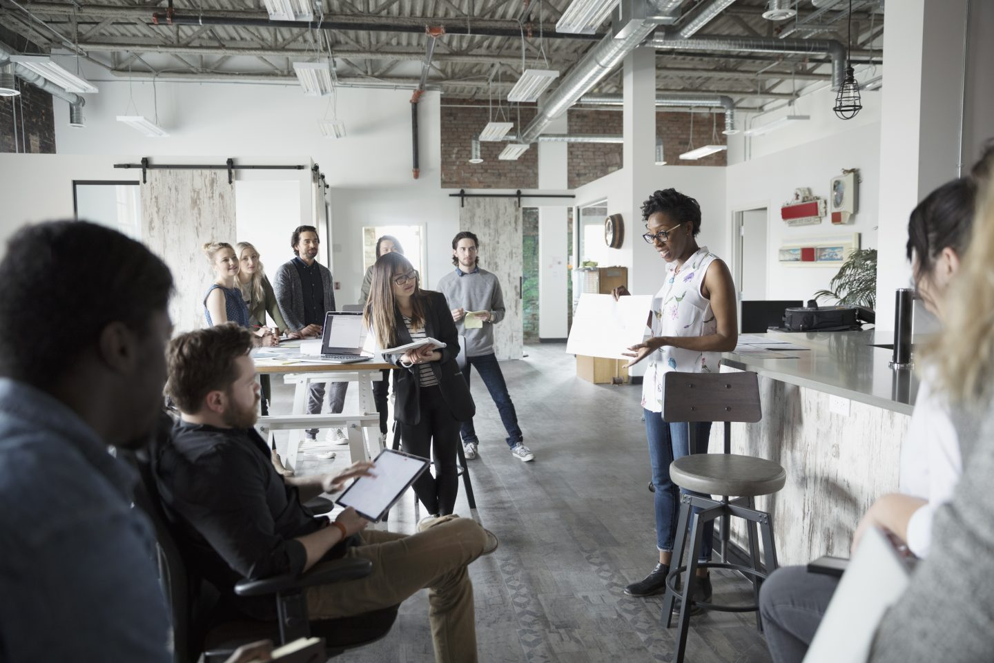 Female designer leading meeting, showing blueprint in meeting in open plan loft office