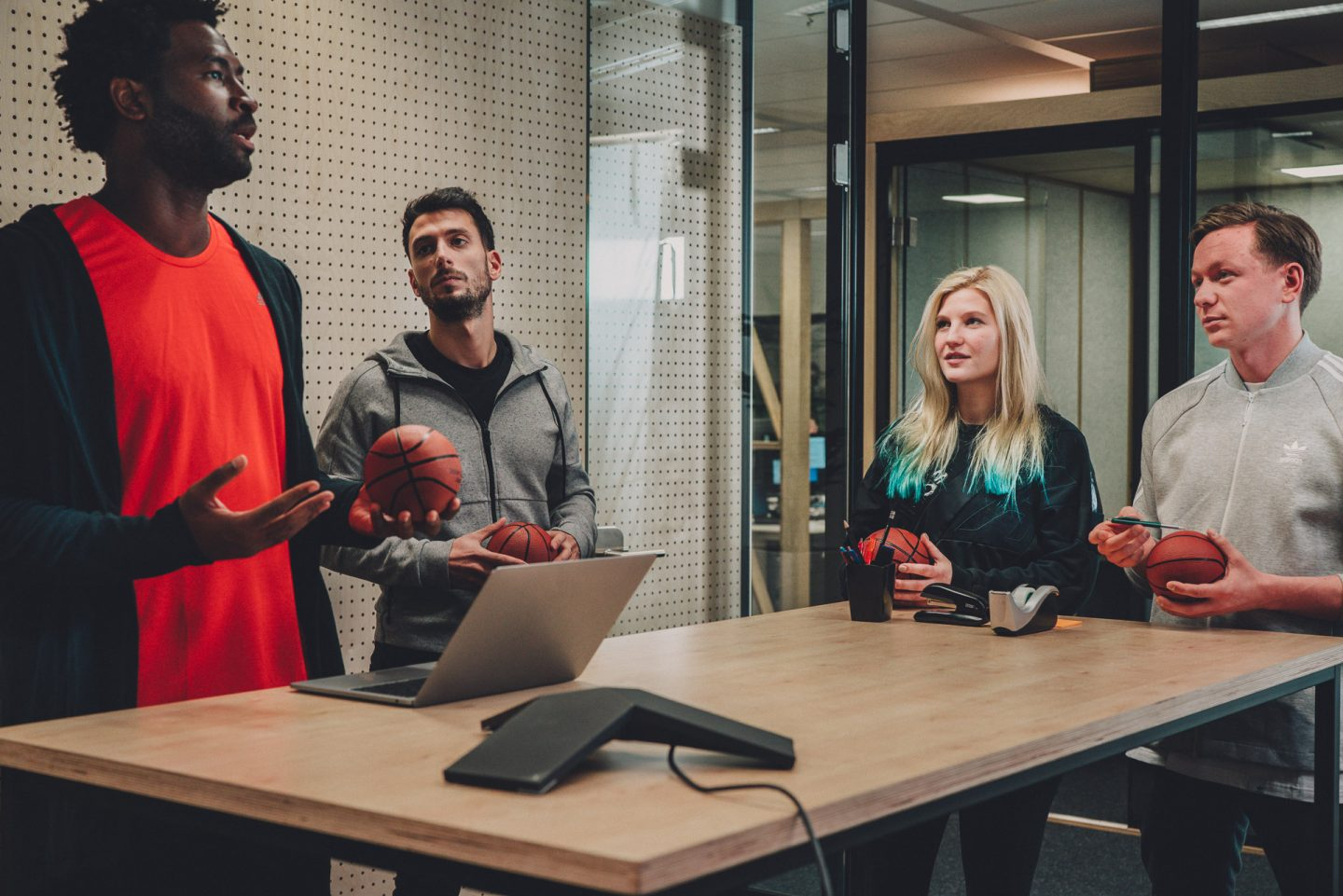 Employees brainstorming ideas during a meeting in a modern office environment. HereToCreate, adidas, teamwork, basketball, digital, leadership, strategy