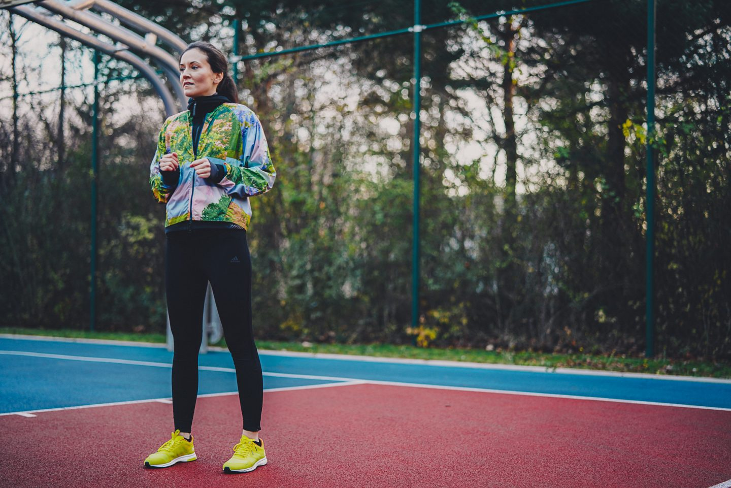 A woman wearing fitnss clothing stands tall in a tennis court with her held up under her chest. sport, fitness, training, thinking.