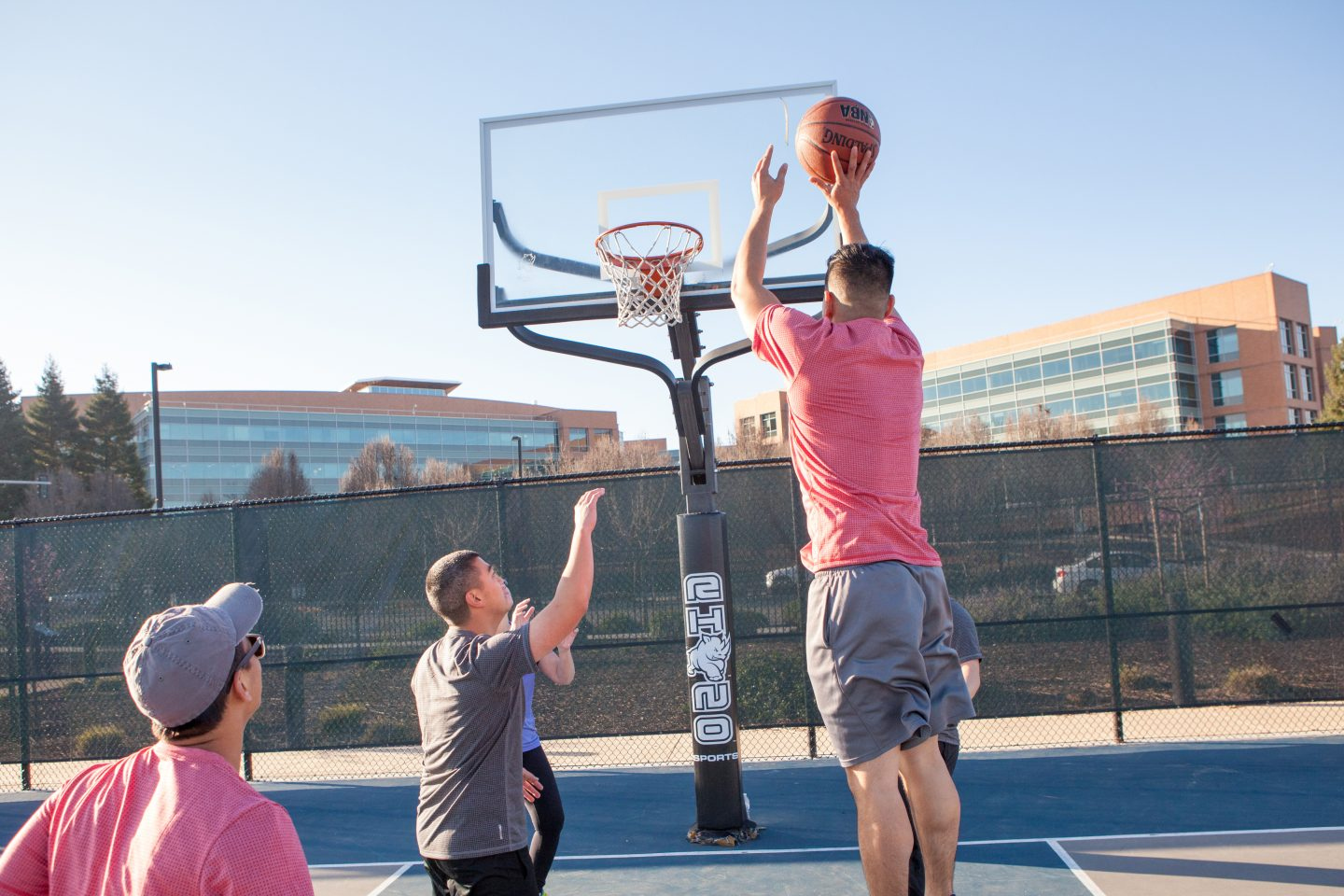 Four men play basketball in a basketball court and one of the men jumps in the air to make a shot. basketball, team, team sport, sport, hobby.