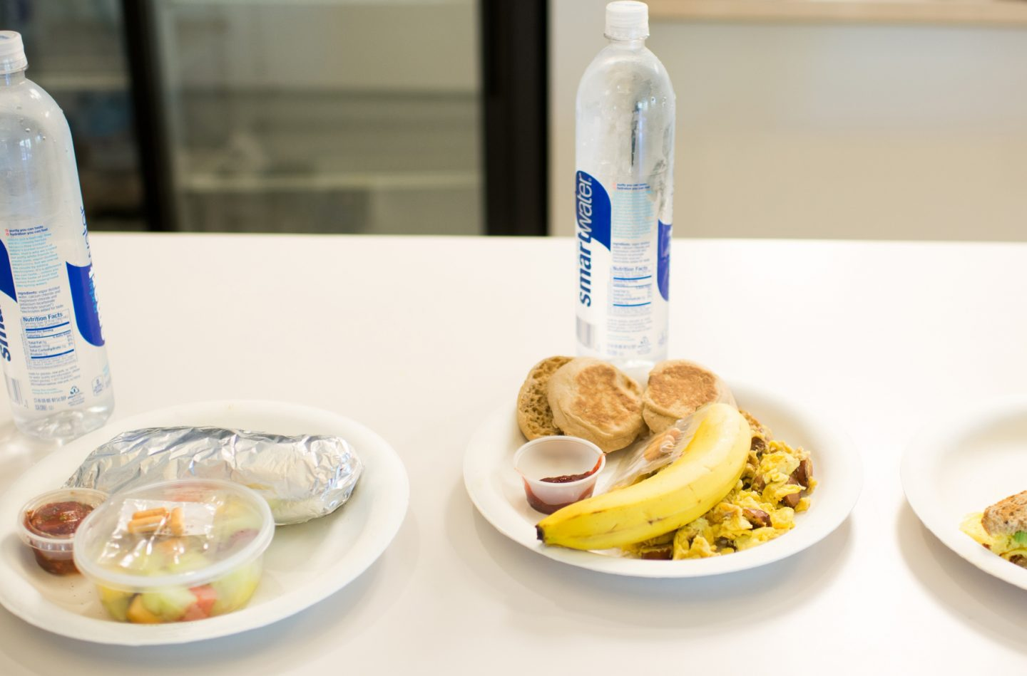 three health meals are set onto a table each with a bottle of water. nutrition, food, healthy snack, water.