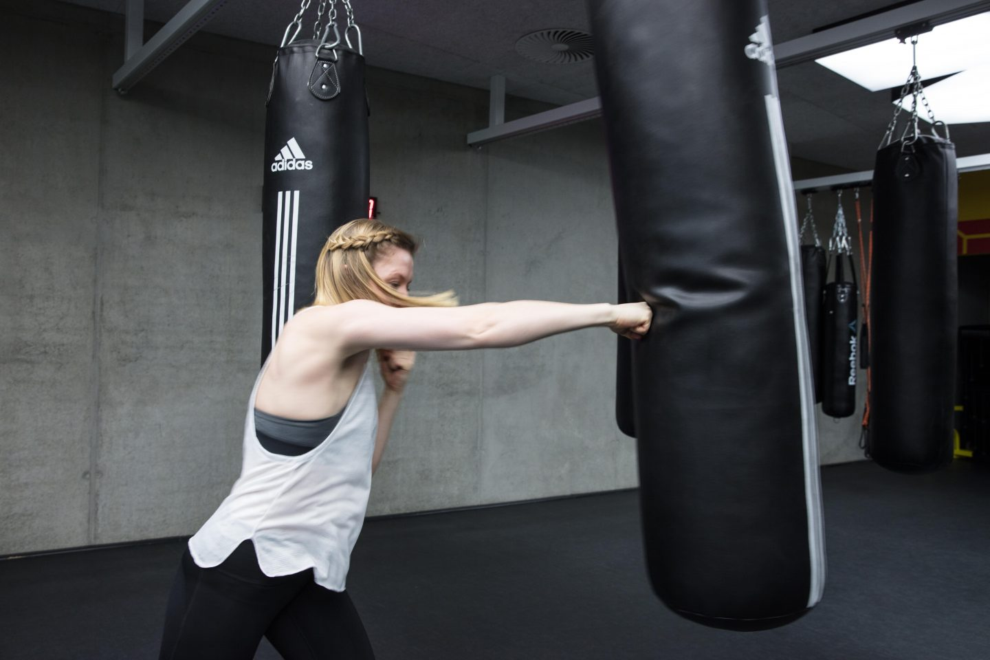 A young woman punches a boxing bag in a gritty gym. martial arts, power, strength, fitness, gym, workout