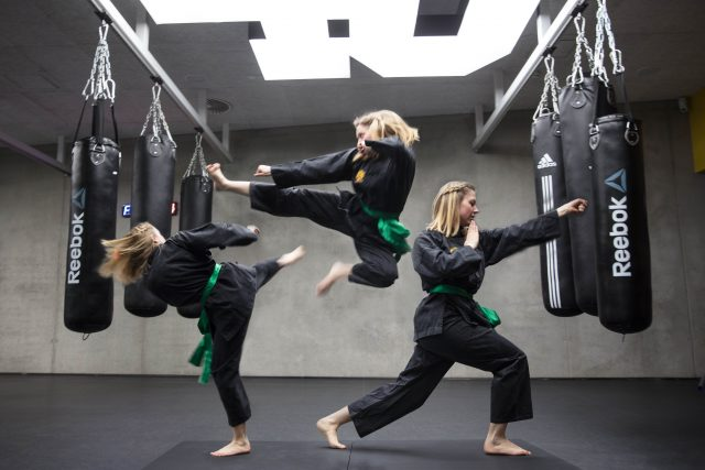 A young woman does three different martial art movements a punch a kick and an air kick all at once in a gritty gym. martial arts, movements, power, strength