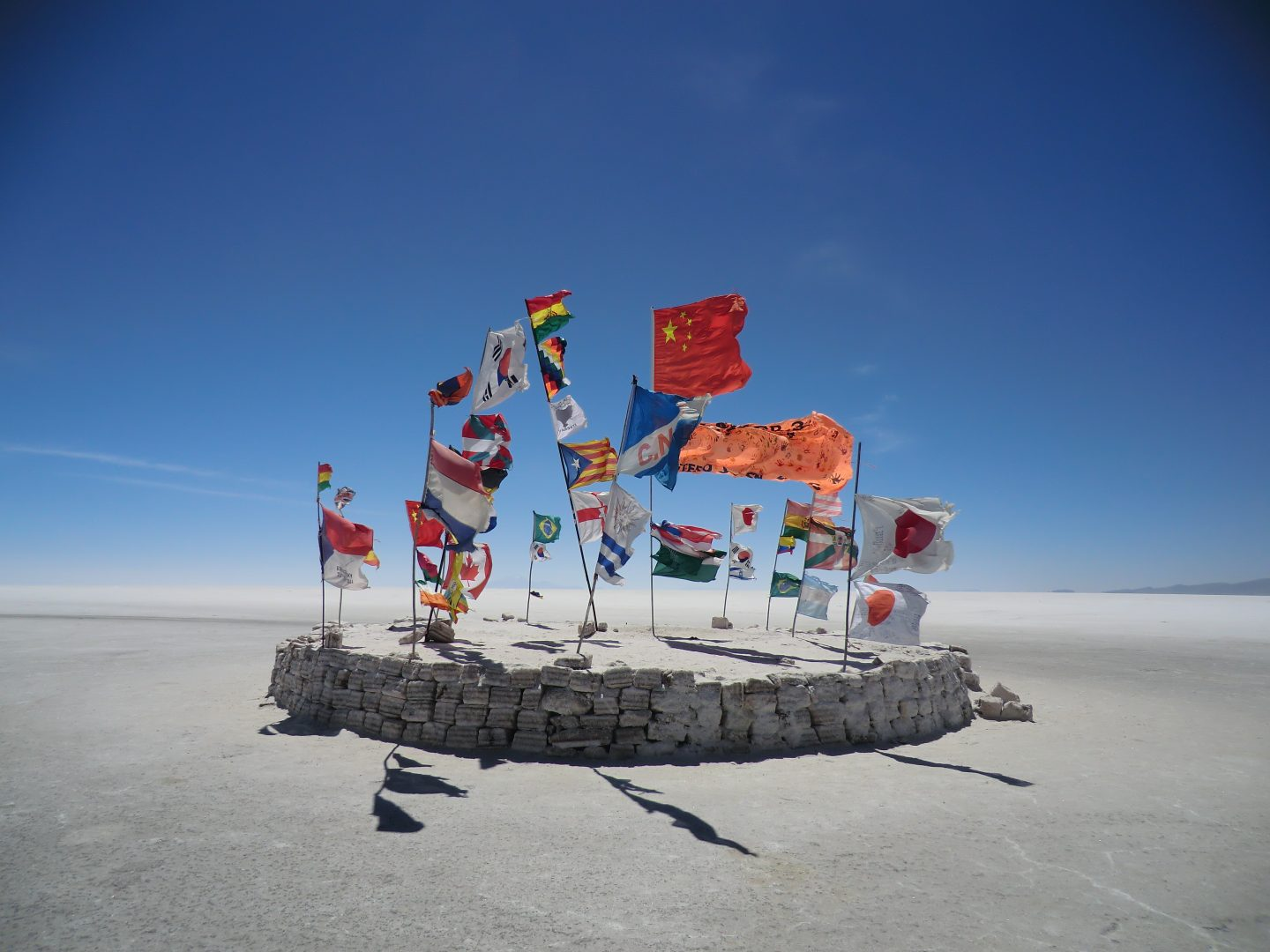 A round wall in the middle of the dessert holds up many flags of different countries. nations, flags, culture, travel, dessert.
