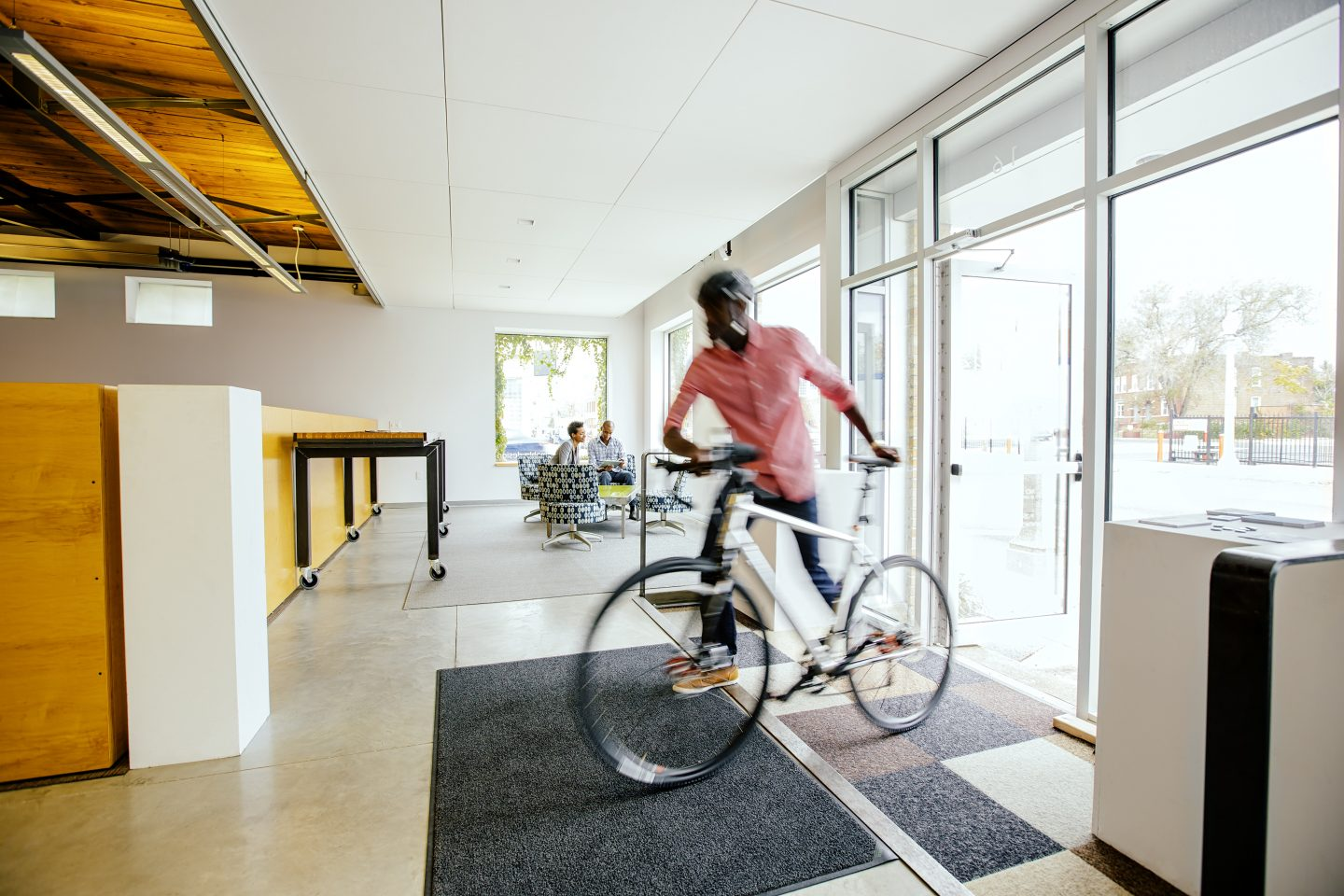 Blurred view of businessman pushing bicycle into office. office, workplace, rushing, bicycle