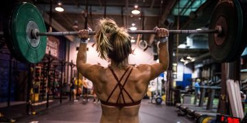 A female cross fit athlete holds a weight over her head. training, weights, cross fit, strength