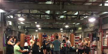 A group of people in a gym in front of a boxing ring train boxing. adidas, talent, talent program, leadership, coaching, GamePlan A