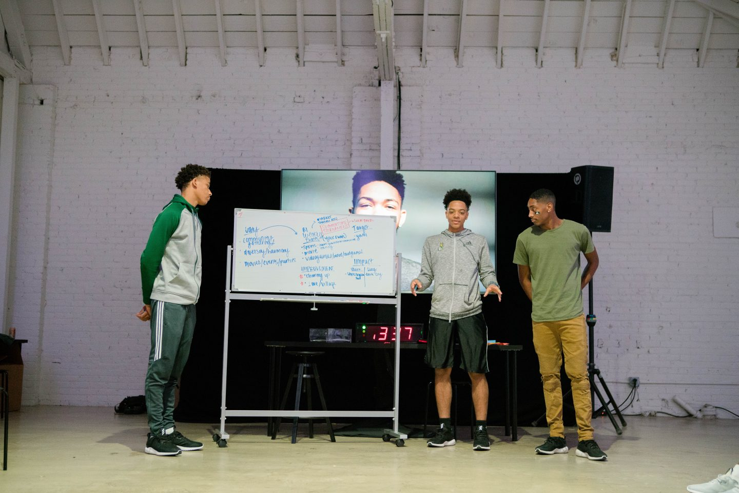 Three young boys stand beside a whiteboard presenting their ideas. teamwork, confidence, teaching, learning