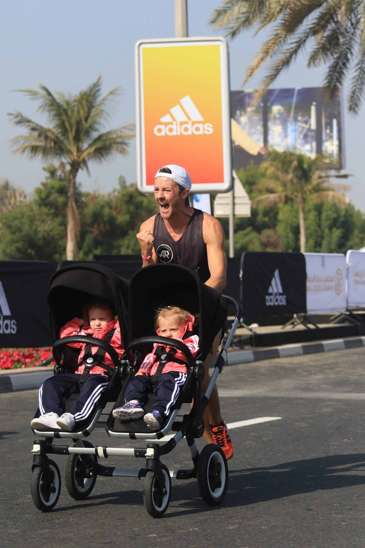 A father pushes his two daughters in a buggy while running in a marathon. running, marathon, family, father, achievement, goal