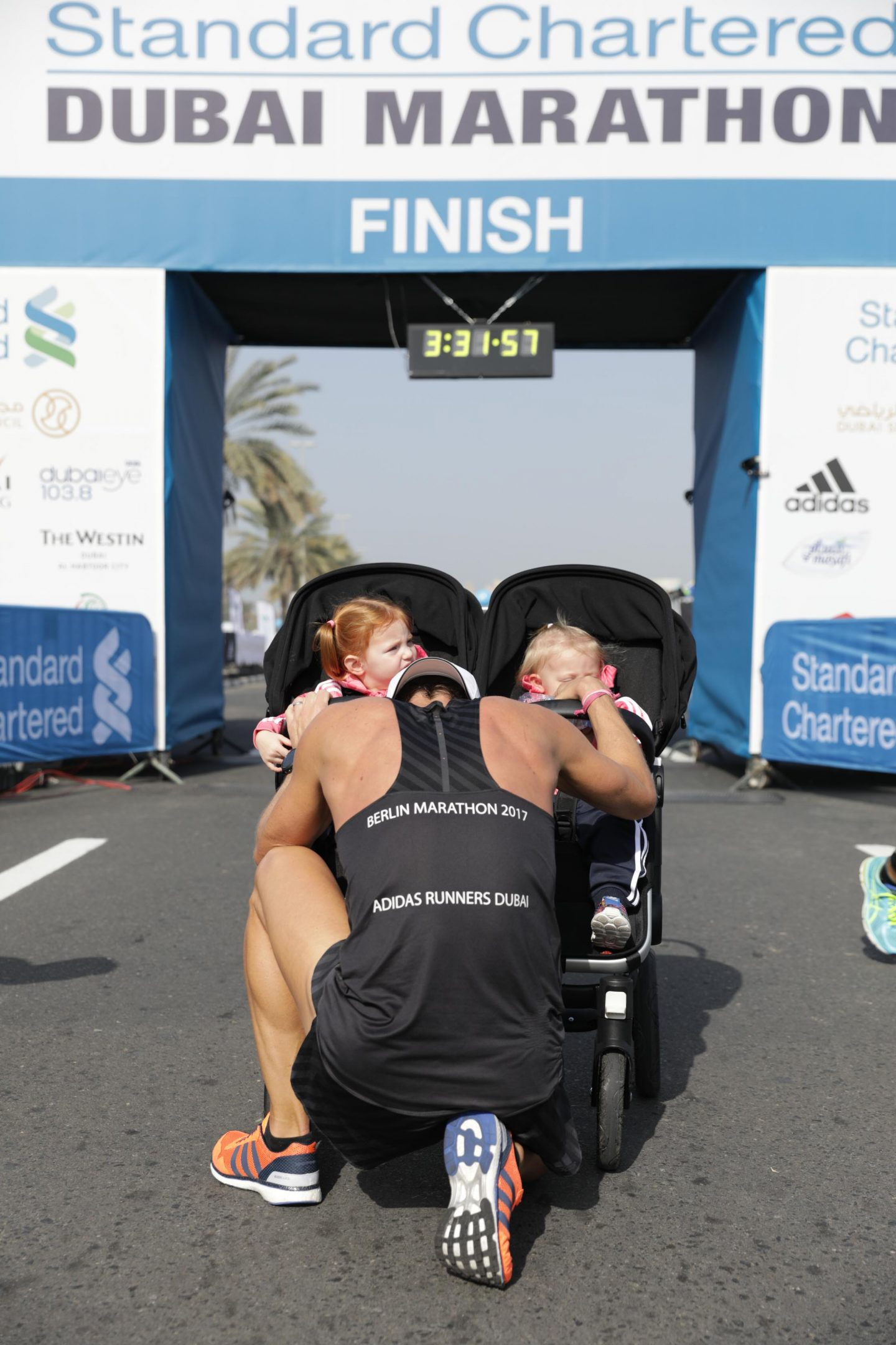 A father kneels down infront of his daughters after finishing a marathon. running, marathon, completion, success, goal, happy, proud