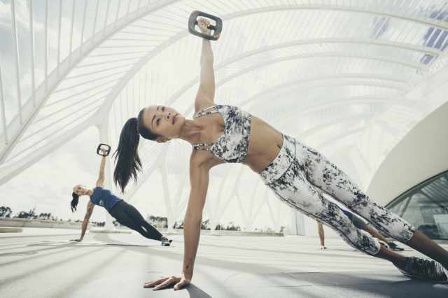 Two women working out in an open space doing side planks with weights. fitness, training, weightlifting, bodyweight training, health