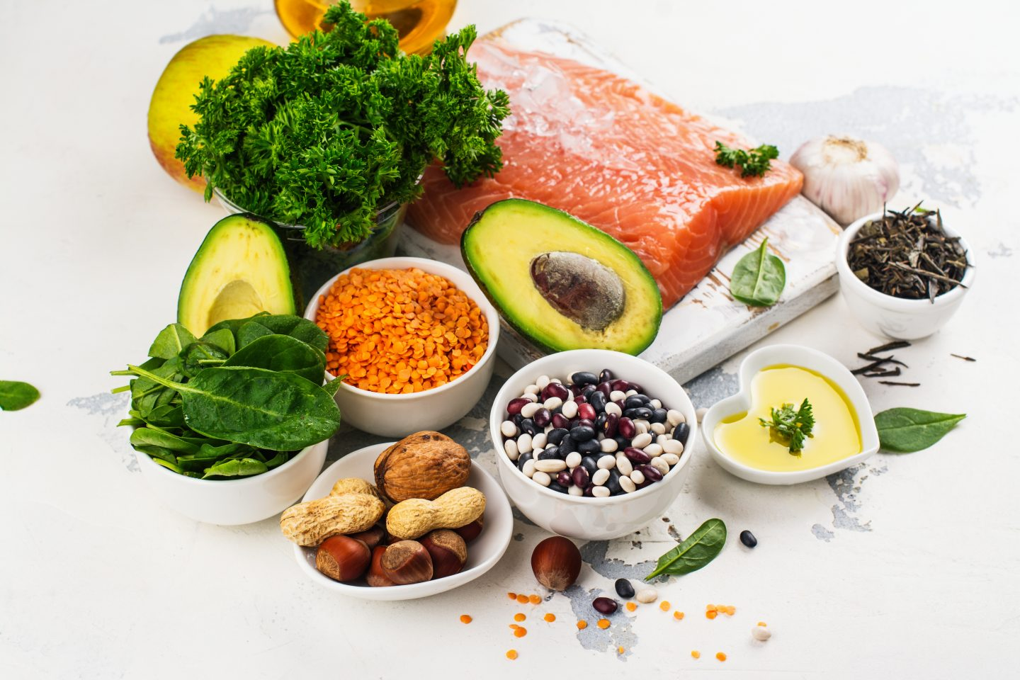 Low colesterol food, like avocado, salmon and nuts placed on a white surface. adidas, GamePlan A, health, fitness, nutrition, weight loss, muscles