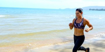 A woman runs across the sand on a beach. fitness, health, runner, running, beach, outdoors, oceans