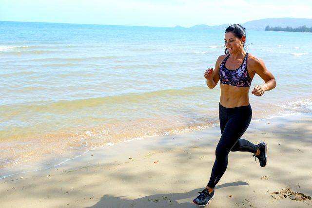 A woman runs across the sand on a beach. fitness, health, runner, running, beach, outdoors, oceans
