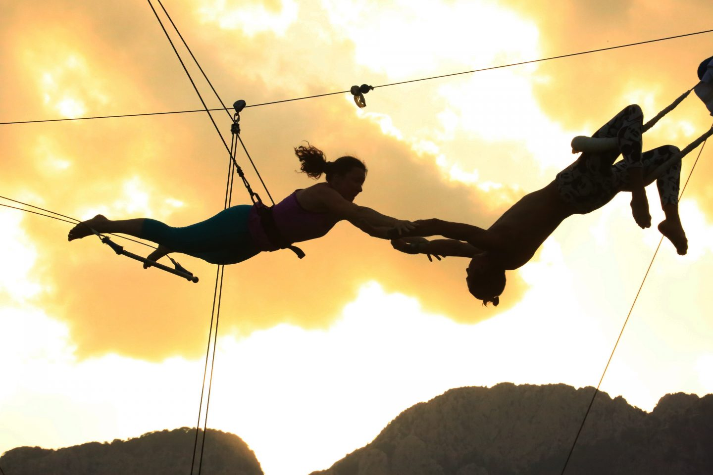 Two people swing in the air on a trapeze during the sunset reaching out to catch one another. sunset, sport, trapeze, faith, trust