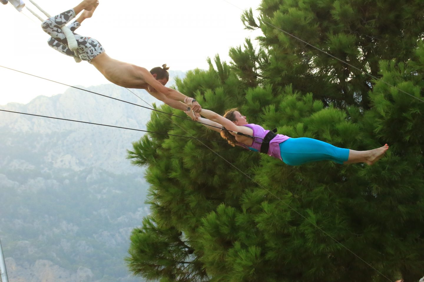two trapeze artists hold each other in the air. trapeze, jump, faith, trust