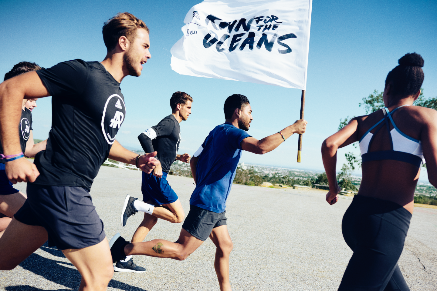 A group of runners hold a run for the oceans flag. parley, run, oceans, running, runners