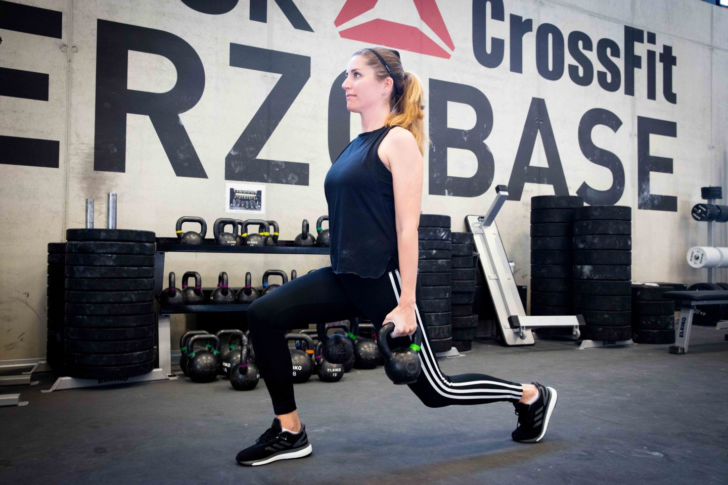 Woman holding kettle bells while doing lunges in a CrossFit box. adidas, GamePlan A, work life, health, lifestyle