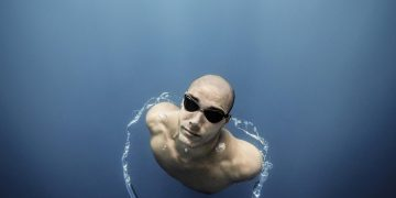 A man swims to the surface wearing black goggles surrounded by an air bubble wrapping his body. water, swim, swimmer, ocean, swimming pool