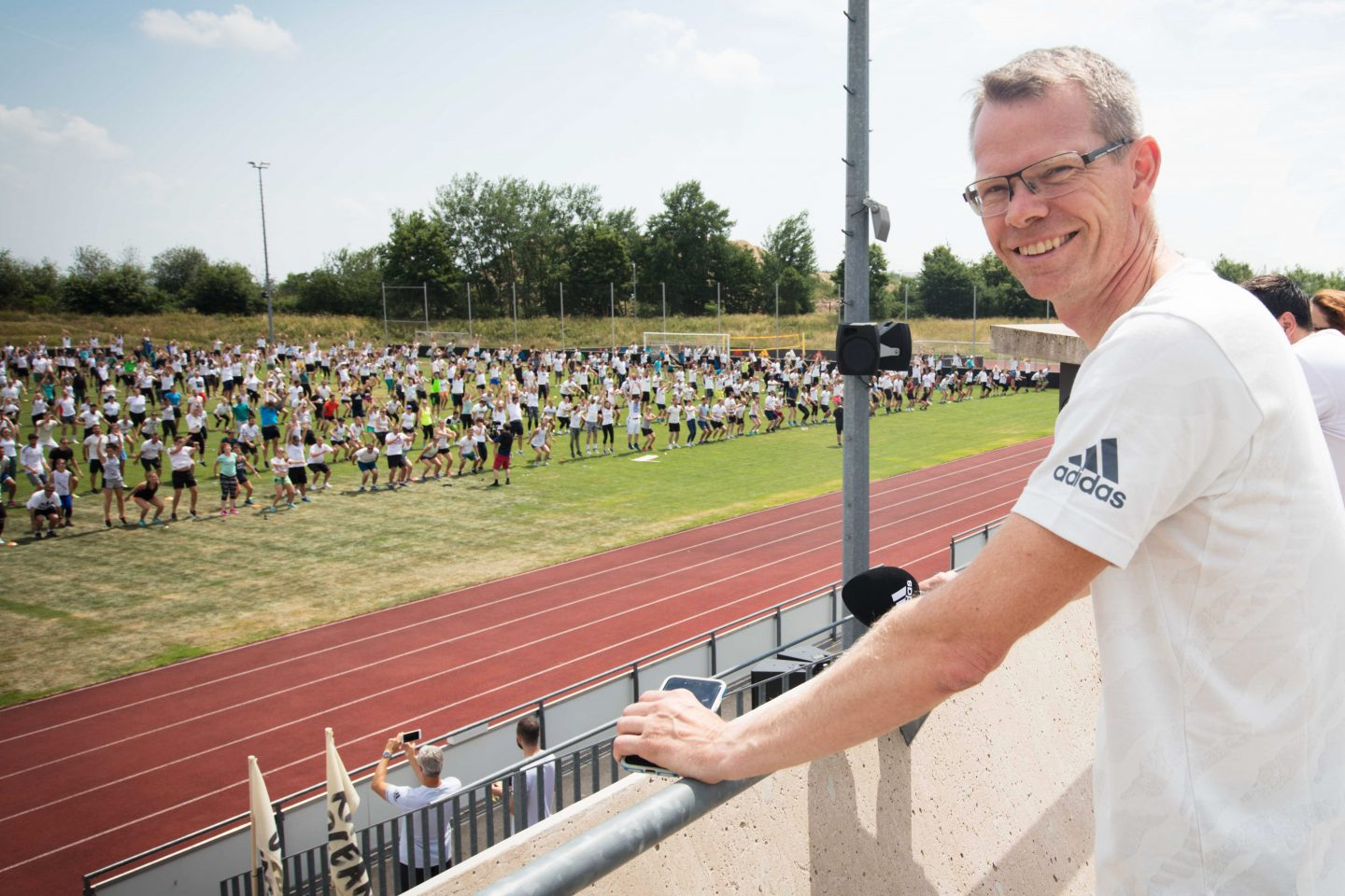 an Executive Board Member at adidas stands smiling at the efforts of adidas employees in preparation for Run For The Oceans. team, sports, adidas, run for the oceans