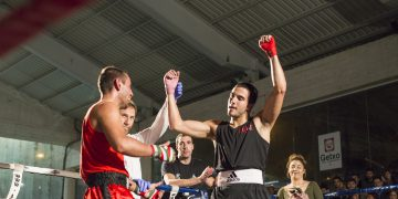 A boxer holds up his hands in victory after a fight. boxing, sport, winning, success