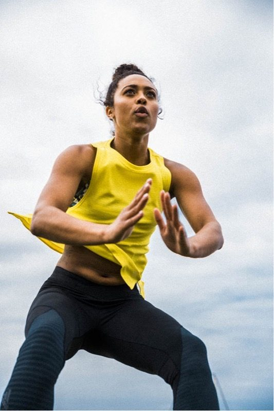 Woman wearing a yellow tank top and black tights is doing a jump squat. Fitness-Jump Squats-Workout-Woman